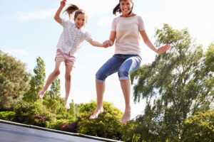 A mom and daughter jumping on a trampoline
