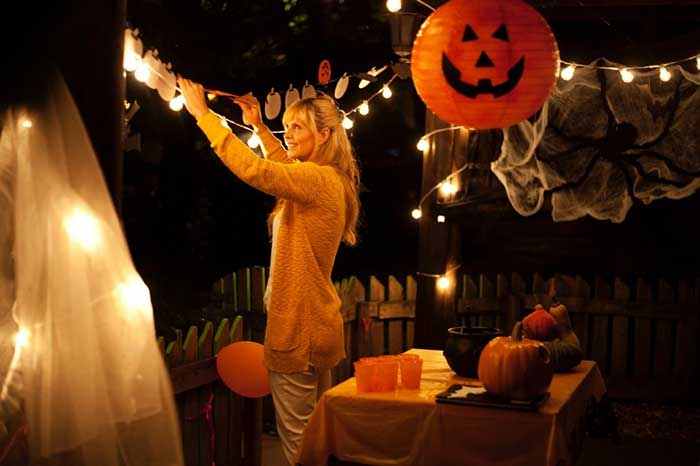 woman decorating the yard for Halloween