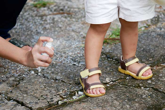 mom spraying ointment on child's feet