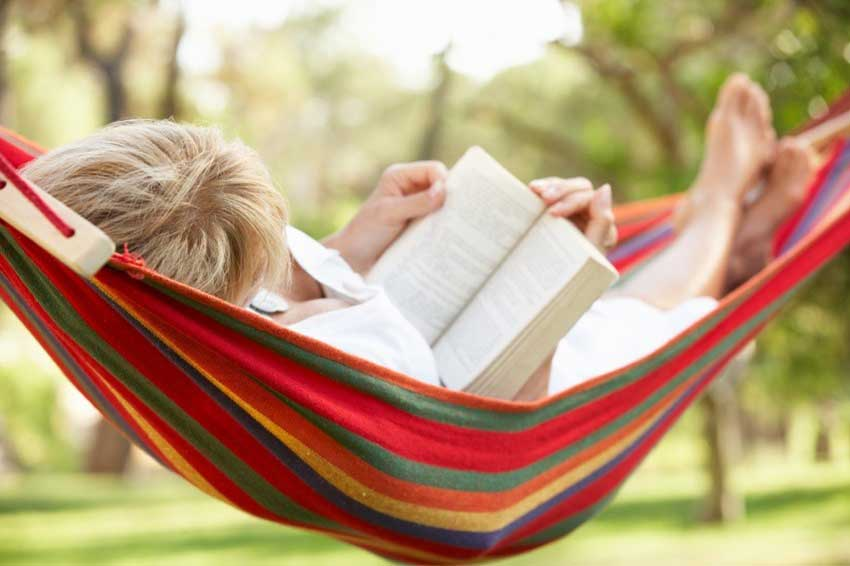 Woman reading book in swing